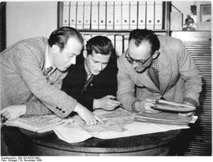 Zentralbild Schlegel 10.11.1956 - Durch richtige Standortverteilung zu höheren Erträgen - Die Standortverteilung der landwirtschaftlichen Produktion als Voraussetzung einer axakten Perspektivplanung und für höhere Erträge haben die Bezirke Karl-Marx-Stadt und Dresden als erste in der DDR abgeschlossen. Danach teilt sich der Bezirk Karl-Marx-Stadt in drei Hauptproduktionsgebiete auf, die sich wiederum in 32 Produktionsgebiete gliedern. Die Mitarbeiter des agronomischen und zootechnischen Beratungsdienstes in den Kreisen und MTS-Bereichen legen auf dieser Grundlage die künftige Entwicklung der Feld- und Viehwirtschaft im einzelnen fest. UBz: (vlnr): Oberagronom Wagner von der MTS Neuendorf; Oberagronom Schwarzbach von der MTS Großschirma und Bezirksagronom Metnel haben eine Karte des Bezirks Karl-Marx-Stadt ausgearbeitet, auf der die 32 Produktionsgebiete eingezeichnet sind. Diese Karte soll in den Wintermonaten auf Bauernversammlungen zur Diskusssion gestellt werden.